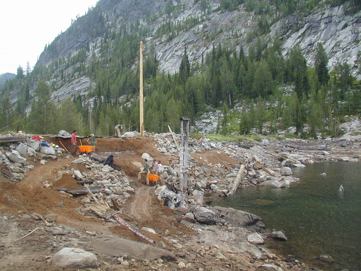 A group of workers moving debris along the edge of a small lake on an old dam, at the base of a steep face.