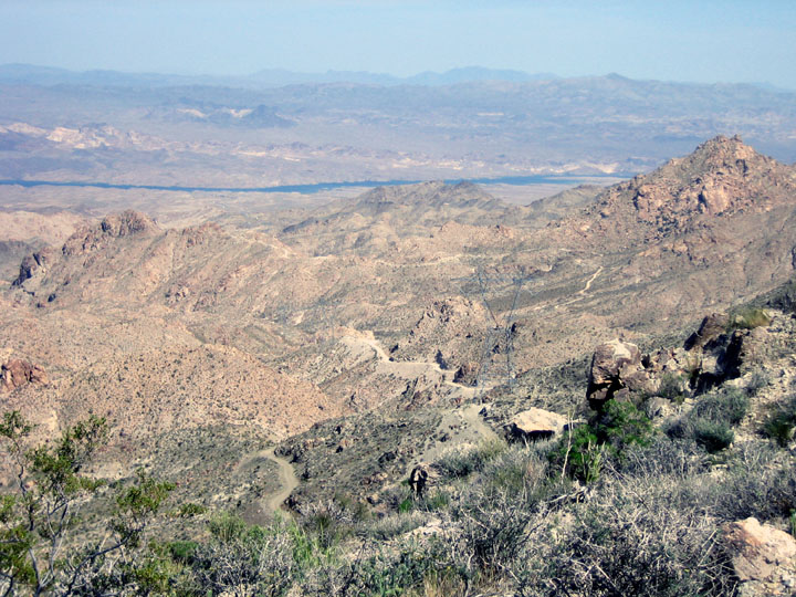 A dirt road winds through a rocky desert landscape towards a body of water in the distance.