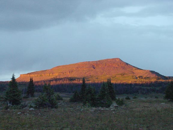 A large, low, isolated peak bathed in the last warm evening rays, above a valley below in deep blue shadow.