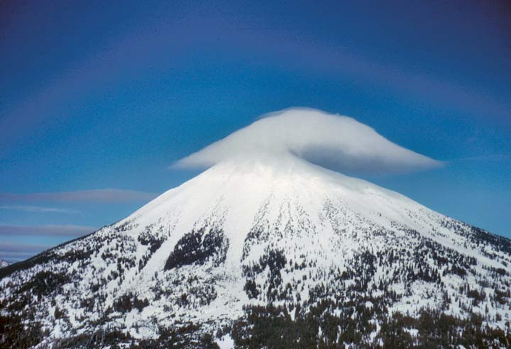 A cloud mimicking the shape of the snow-covered summit hangs over the mountaintop.