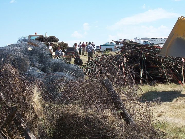 Agency staff standing amid large piles of rusty barbed wire, rolls of fencing, and stacks of fenceposts, all removed from the wilderness.