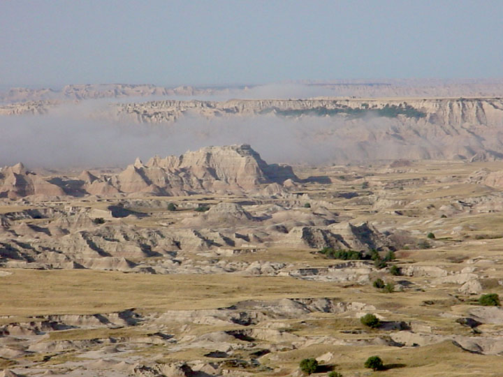 Viewing out over the badland landscape, pale grassland broken by protruding rock formations and low clouds.
