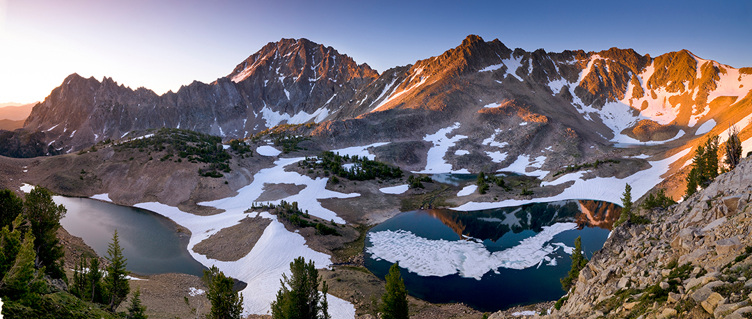 Sunrise over a mountain rage with lake filled bowls and snow.