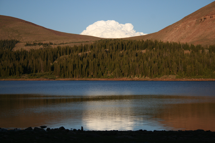 A lone cloud creeps over a pass above a large dark lake.