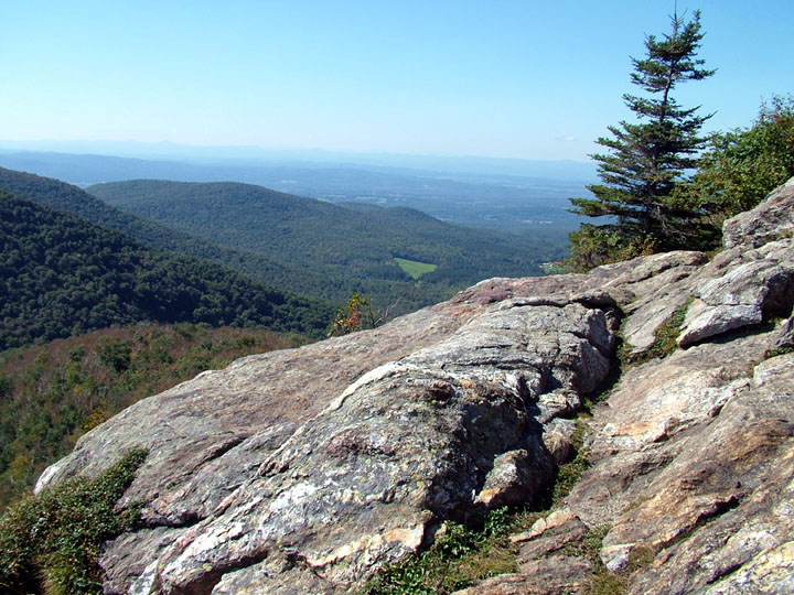 A view from a rocky vista shows forested hills rolling into the hazy blue horizon.