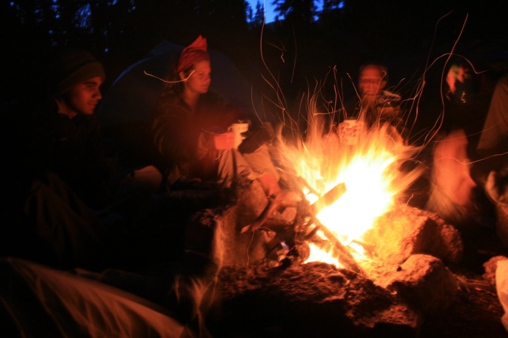 Campers sit around a small blazing fire Weminuche Wilderness Area Colorado.