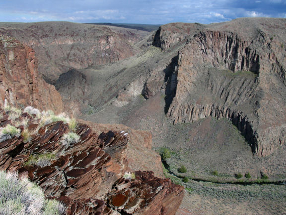 Brownish-red rocks sit on the edge of a canyon with steep sloping walls and a small stream at the bottom.