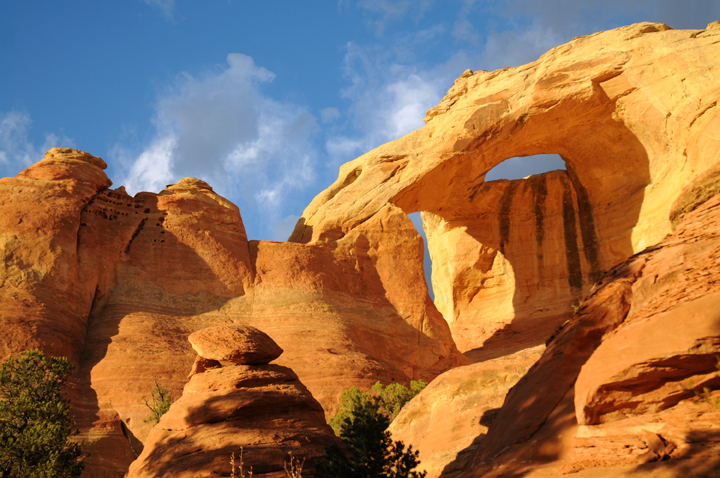 Two arches formed on the side of red-orange rocks reflecting the desert sun.