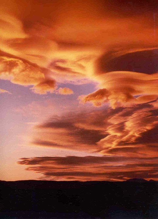 A sunset in the John Muir Wilderness colors the sky and the stretching clouds in light pinks and deep purples.