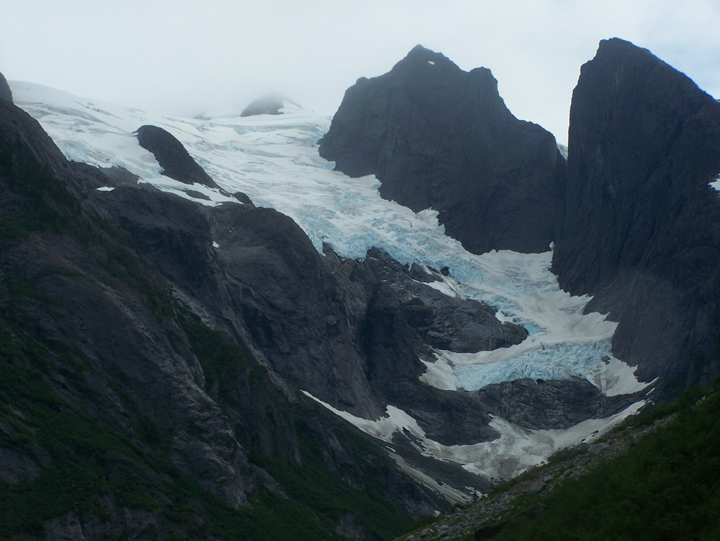 A large light blue glacier dusted with snow sits on the side of a steep mountain slope.
