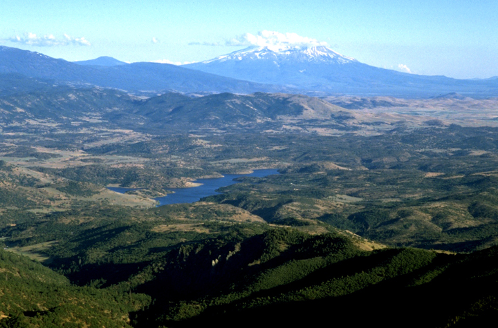 Large forested mountain slopes lead down to a dark blue lake with rolling foothills.