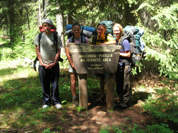 Four backpackers/volunteers pose next to a sign that reads,