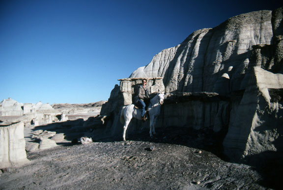 A horseback rider poses next to a large rock formation in the Bisti/De-Na-Zin Wilderness on a clear sunny day.