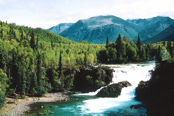 A large crystalline river dropping over a large falls, bordered by dense forest, and low mountains in the background.