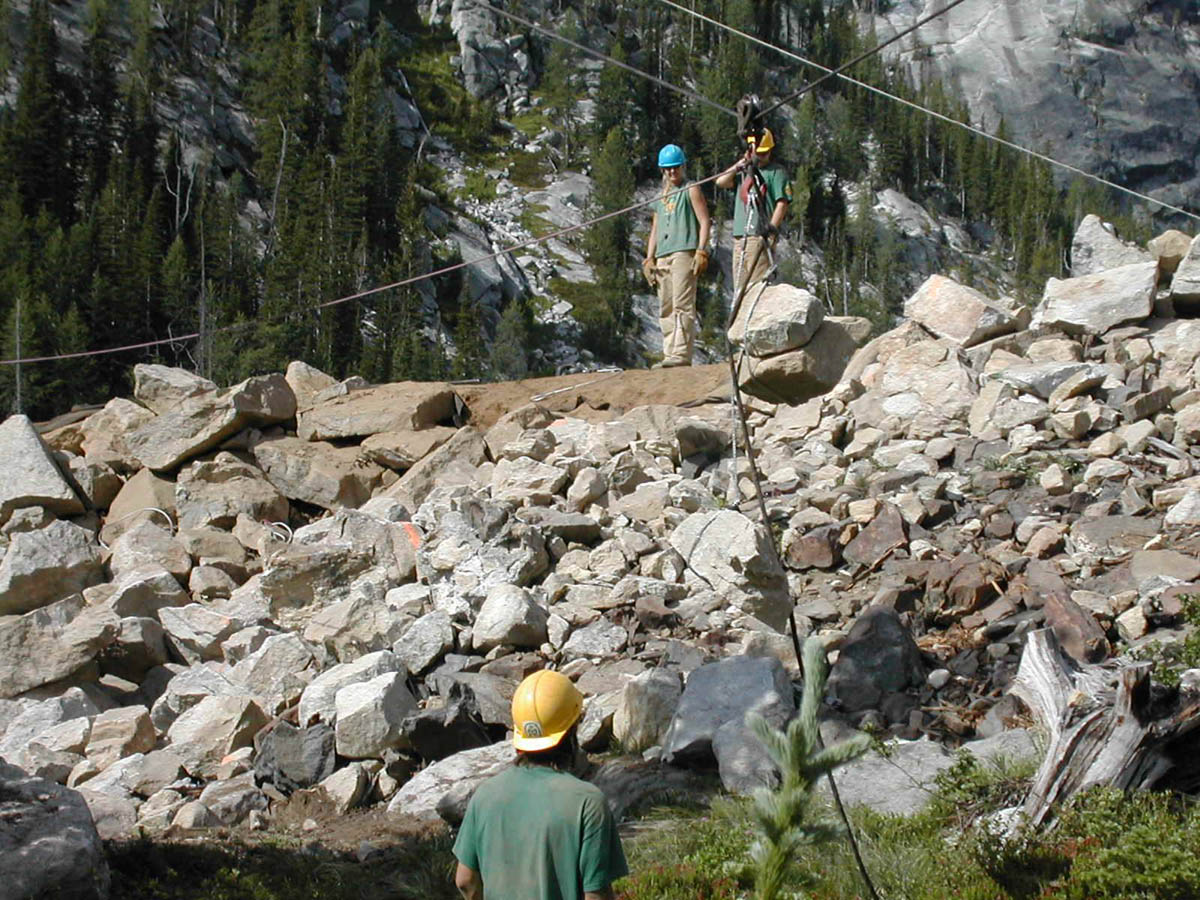 Several people in green shirts and hard hats, standing on a pile of rubble, working to move large boulders with various cables.