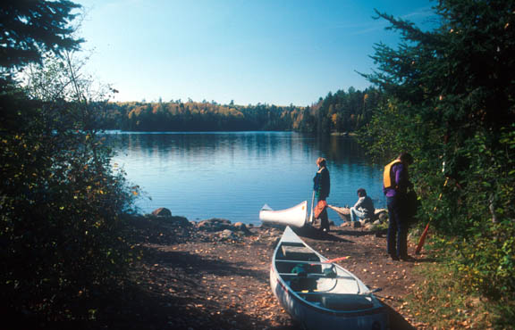 A photo of Sawbill Lake taken from Alton Portage. In the photo are people getting ready to canoe out on the lake. It appears to be early in the morning and the sky is clear and sunny.