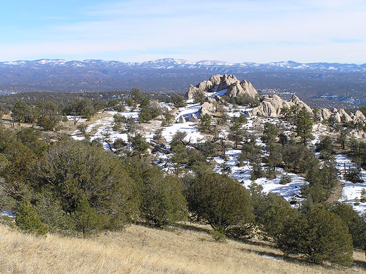 An outcropping of white rocks stands amid snow.