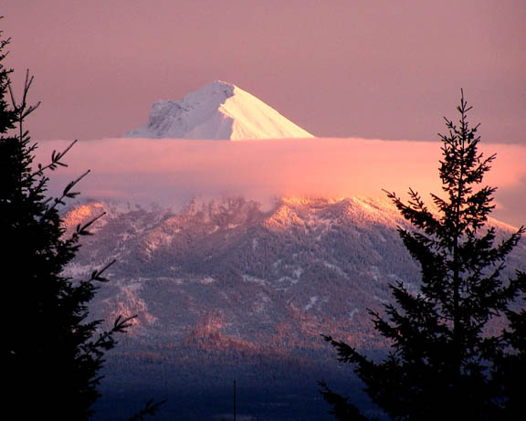 The setting sun casts pink and purple hues on the gray sky behind Mt. McLaughlin. The pink and purple hues also touch the moutain.