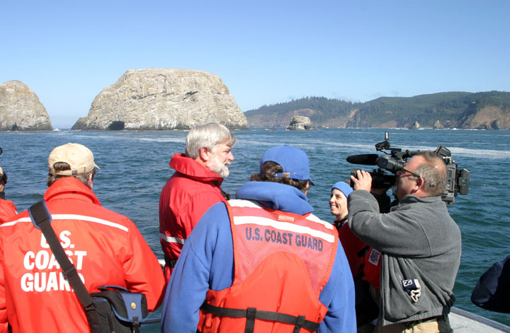 Several men in orange Coast Guard jackets are interviewed by a man with a video camera, with the rock islands and coastline in the background.