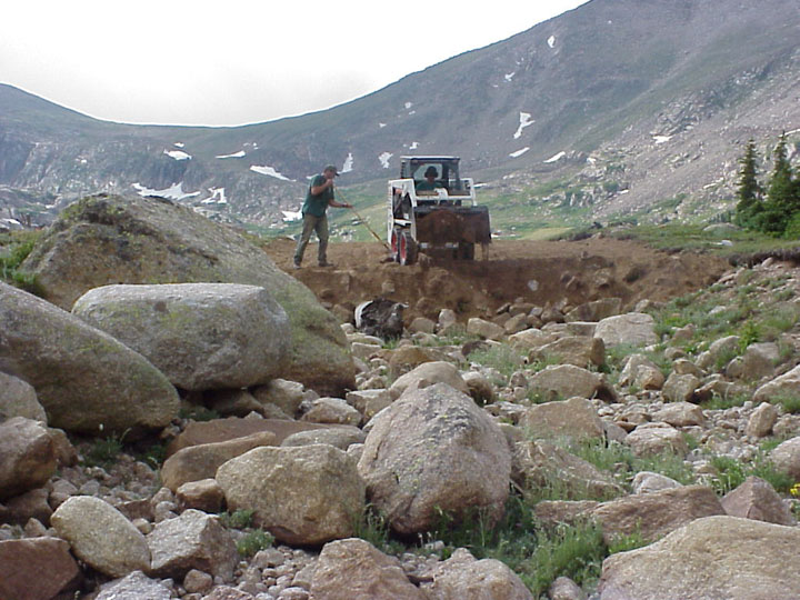 A man uses a shovel to pull dirt from the bucket of a small loader, pouring earth over a jumbled mess of large rock.