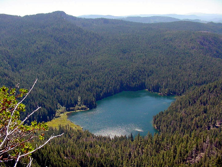 A small blue lake nestled in a valley, with dense forest-covered hills rolling off into the hazy distance.