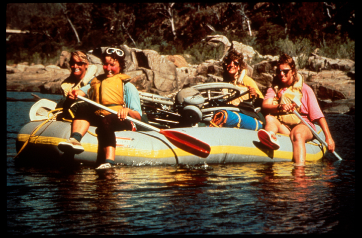 A group of women raft down a river on a sunny day.