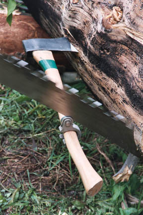 A close-up of a cutting arrangement, using a large hand saw and an axe.