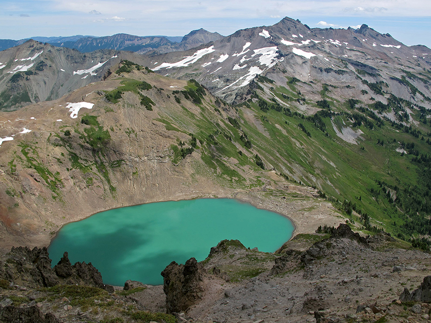 View from very high up on a ridge down on a turquoise lake