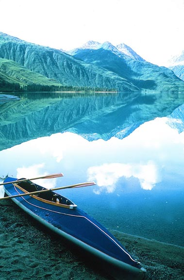 A blue kayak along the shore of a placid lake, the mirror surface reflecting the distant mountains peaks sweeping down to the waters edge.