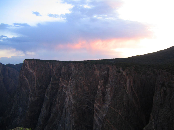 Vertical cliffs rise out of shadow beneath the fading remnants of a blue and pink sunset.