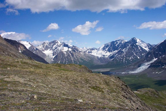 An open alpine ridge overlooking jagged peaks in the distance, emptying small glaciers into the valley below.