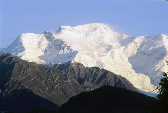 The peak of Mount Blackburn is carpeted in snow on a cloudless day.