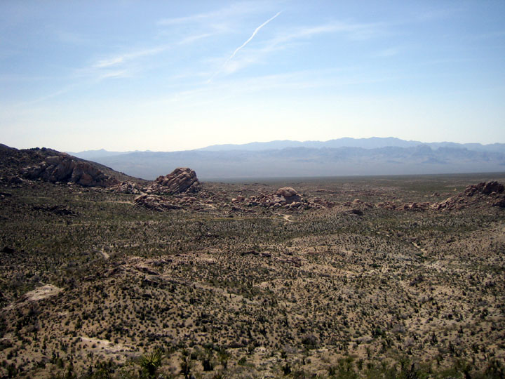 Looking out over a desert landscape towards several rock outcroppings and a hazy mountain range in the distance.