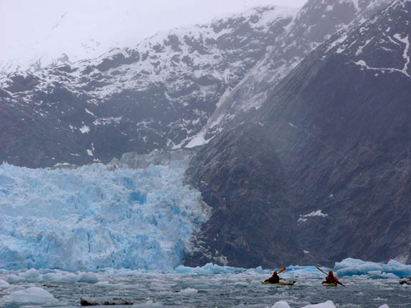 Kayak rangers in the Tracy Arm of the Tracy Arm - Ford's Terror Wilderness, Paddling toward South Sawyer Glacier. In the background is a large mountain base where it appears that partially fozen water is cascadin over it. As the water pours over the base, it looks unnaturally blue, like a blue-raspberry snowcone.