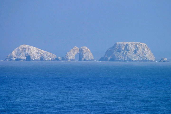 A long distance look through a blue haze of the Three Arch Rocks breaking the horizon.