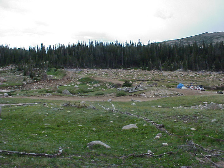 Two small pieces of equipment sitting on a small dirt pad, surrounded by an open rocky meadow, surrounded by forest.