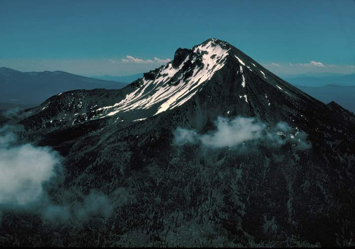 A high rocky peak laced with snow near the summit, with puffy white clouds floating nearby.