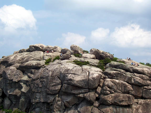 Many hikers sit atop a huge grey boulder formation at Old Rag Mountain.