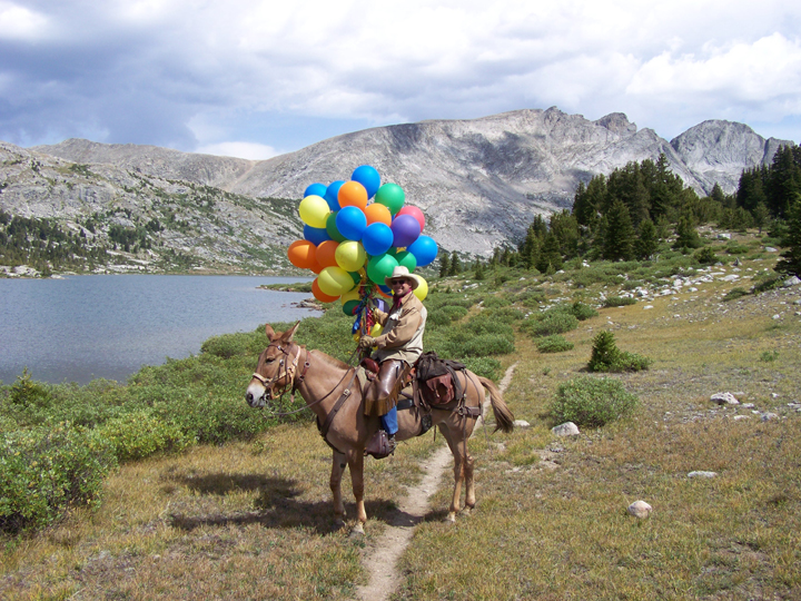 A man sits atop a mule with a large bouquet of colorful balloons with a lake and mountains in the background.