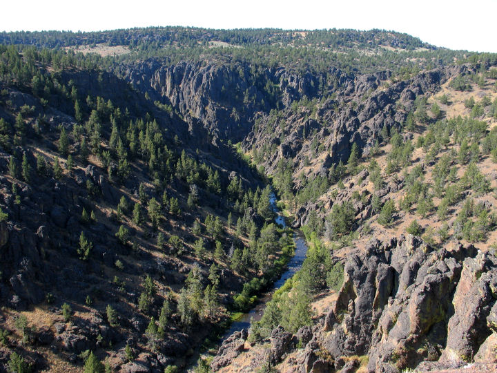 Large rocks and trees dot the side of a valley as a river flows through the bottom.