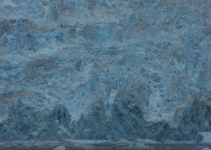 A light blueish-grey ice face covered in sharp jagged points.