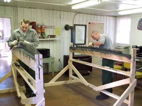 Two agency staff, sharpening large hand saws in a wooden vice, in a small workshop.