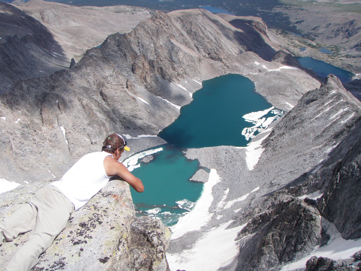 A hiker peers over the edge of a steep dropoff with glacial lakes below.