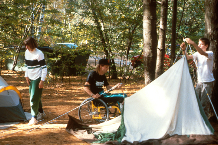 A man in a wheelchair helps set up a tent in a campsite.