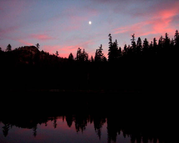 A sunset darkens the surrounding area of the lake, leaving only the pink clouds and navy sky illuminated.