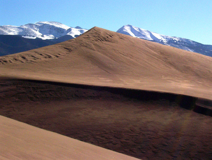 A large, sweeping, golden sand dune, contrasted against a blue sky and snowcapped mountain peaks in the distance.