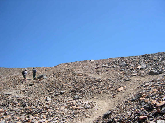 Two backpackers explore the multiple informal trails developing along the rock-laiden shoulder of Mt. Hoffman.