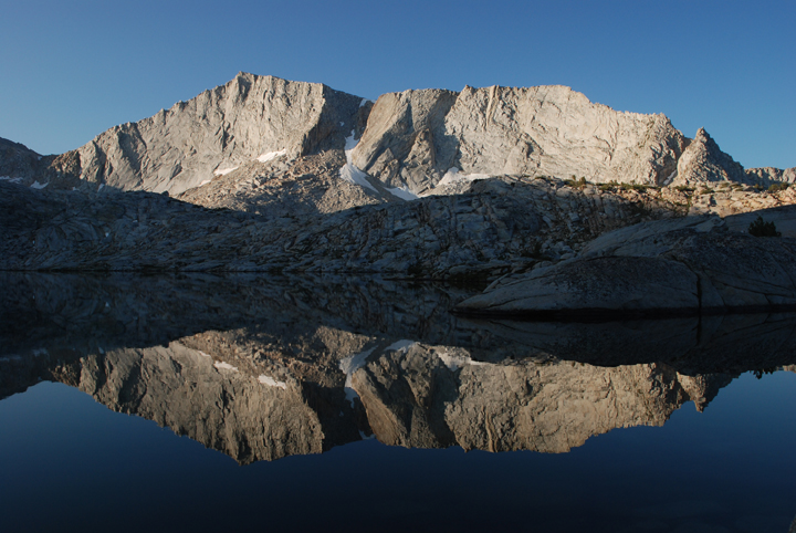 The still water of Hell For Sure Lake reflects a small mountain on a clear sunny day in the Jonh Muir Wilderness.