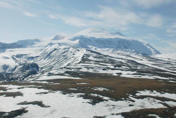 A large snow-covered mountain range as seen from a broad saddle.
