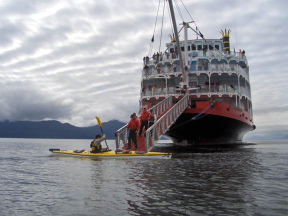 A Forest Service kayak ranger paddles out to and boards a cruise ship to give an educational presentation to passengers.